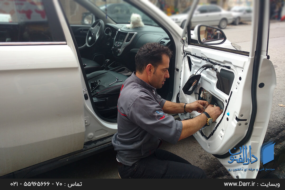یکی از شاگردان موسسه درالفنون در حال یادگیری تعمیر سیم کشی داخل درب خودرو