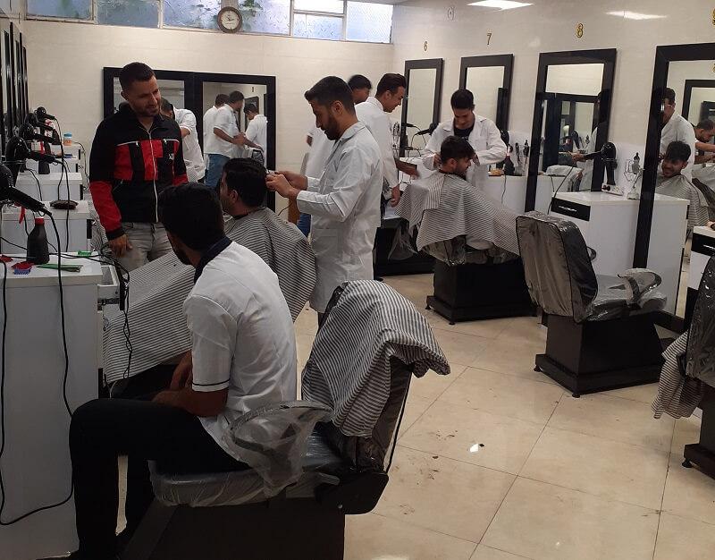 یک هنر جئ در حال اصلاح موی مدل در کلاس آرایشگری مردانه ما