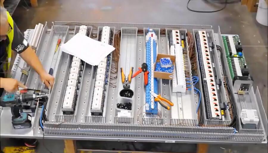 یک برقکار صنعتی در حال مونتاژ جعبه