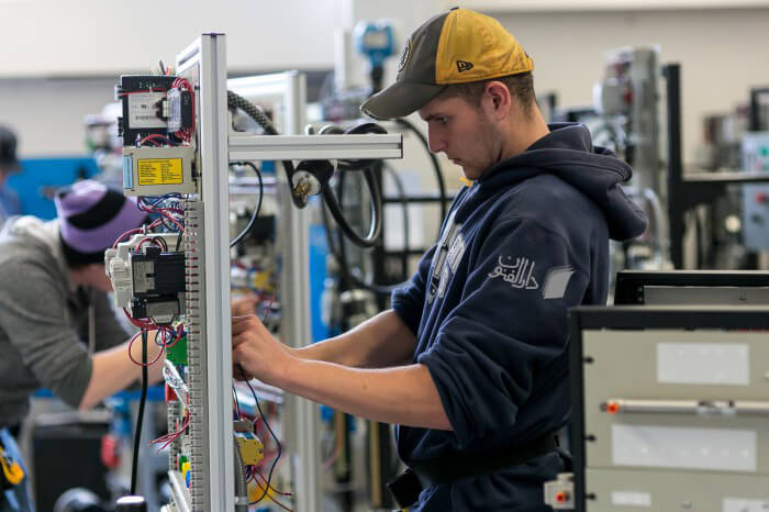 یک کار آموز دوره برق صنعتی در حال یادگیری