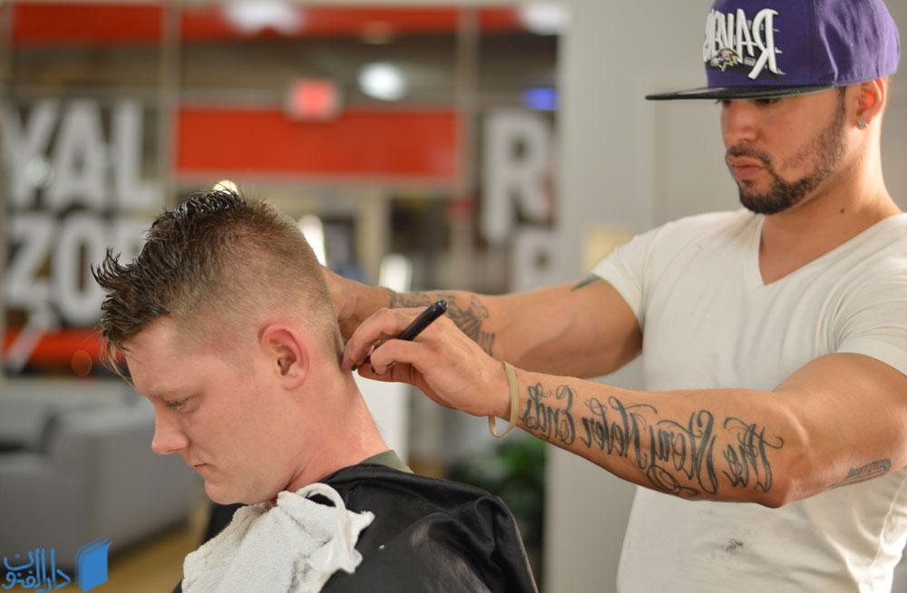 آرایشگر مردانه در حال کوتاه کردن موی مشتری